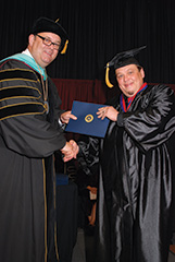 Wayne Gilliland (right) receives a bachelor's degree in human services from Hannibal-LaGrange University President Anthony Allen during graduation ceremonies in May 2015. (HLGU)