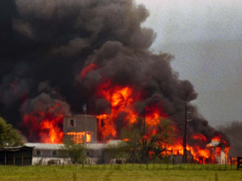 Fire engulfs the Branch Davidian compound near Waco, Texas, on April 19, 1993. The compound burned to the ground after FBI agents in an armored vehicle smashed the buildings and pumped in tear gas. The Justice Department said cult members set the fire. (AP Photo/Ron Heflin)