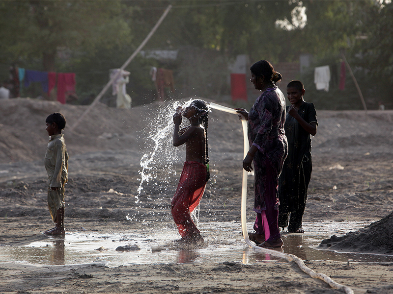 A woman gives her children a shower on a roadside during a heat wave in Lahore, Pakistan, on April 19, 2017. Photo courtesy of Reuters/Mohsin Raza
