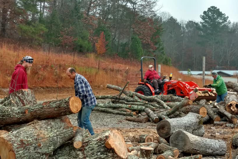"(Left to right) Steve Reach, Dan Grader, Laura Nightengale and Larry Davis split and move wood into the ""wood corral"" at Antioch Baptist Church in the mountains of north Georgia. The Blairsville church has provided wood to those in need for nearly 10 years. Photo by Duane Manders/Antioch Baptist Church"