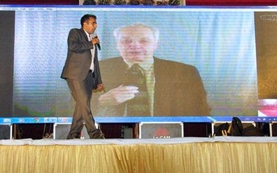 Evangelist Sammy Tippit, shown on screen in India, preaches an evangelistic message to a crowd of thousands, with live translation as he speaks from his office in San Antonio, Texas. Photo courtesy of Sammy Tippit Ministries