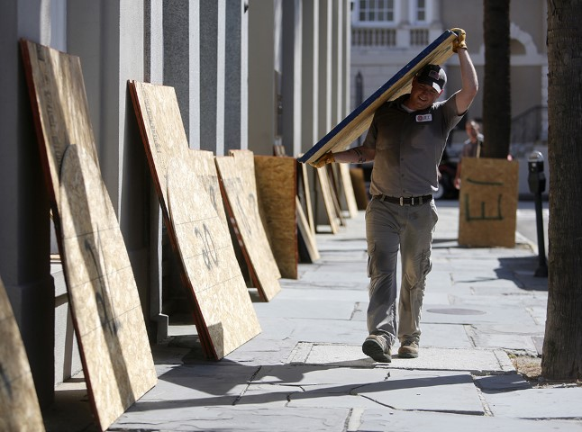 Preston Guiher carries a sheet of plywood as he prepares to board up a Wells Fargo bank in preparation for Hurricane Florence in downtown Charleston, S.C., on Sept. 11, 2018. (AP Photo/Mic Smith)
