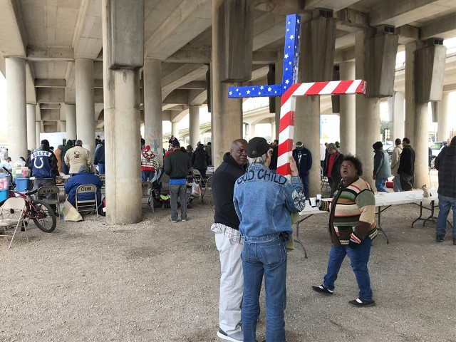 A man carries a star-spangled cross with him to worship at Church Under the Bridge in Waco, Texas, on Nov. 18, 2018. RNS photo by Bobby Ross Jr.