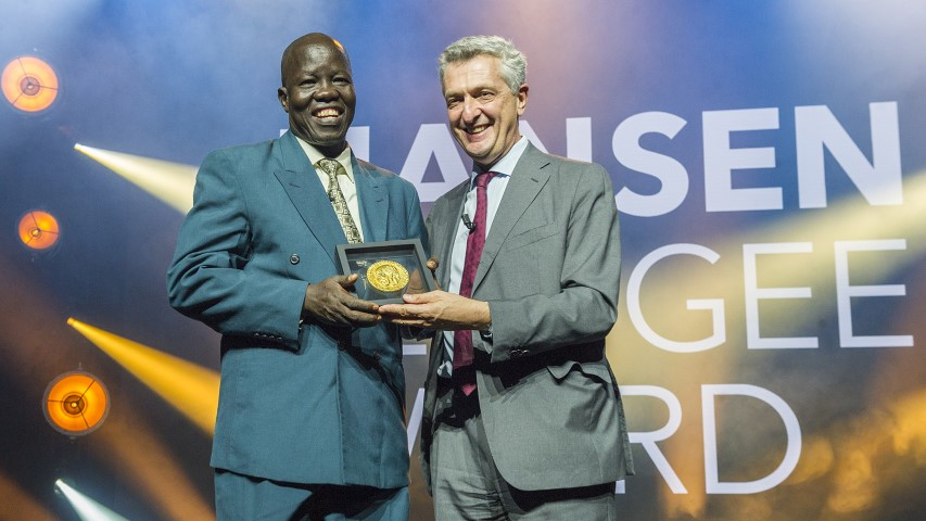 Dr. Evan Atar Adaha accepts the 2018 Nansen Refugee Award from UN High Commissioner for Refugees Filippo Grandi on Oct. 1, 2018. Atar runs the only functional hospital in Upper Nile State, South Sudan, where he and his team carry out an average of 58 operations per week with limited supplies and equipment. For more than 60 years, UNHCR's Nansen Refugee Award has recognized those who show outstanding dedication to the refugee cause. © UNHCR/Mark Henley